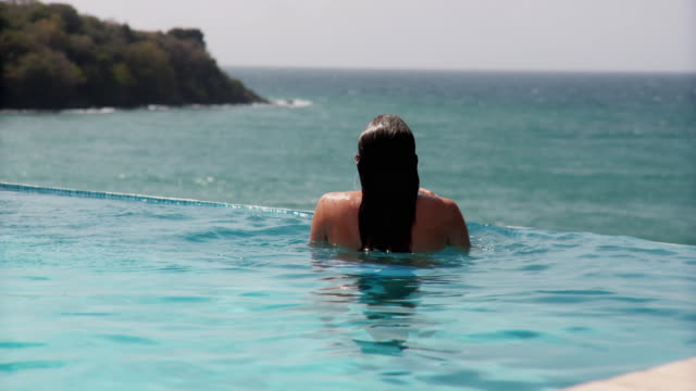 MS RV Young woman surfacing from water in infinity pool overlooking ocean and looking over shoulder to smile at camera/ Scarborough, Tobago, Trinidad and Tobago