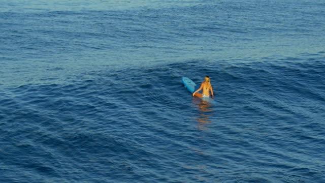 vídeos y material grabado en eventos de stock de a young woman surfing in a bikini on a longboard surfboard. - slow motion - surf en longobard