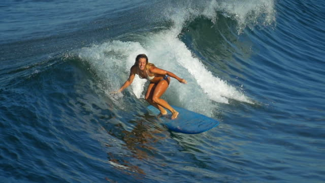 a young woman surfing in a bikini on a longboard surfboard. - slow motion - surfboard stock videos & royalty-free footage