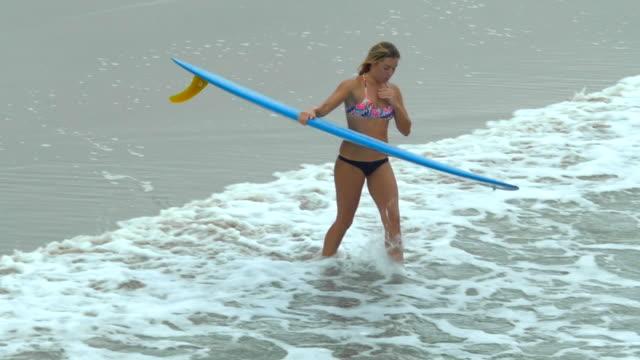 A Young Woman Surfing In A Bikini On A Longboard Surfboard Slow