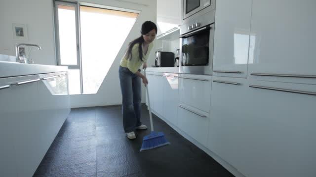 ms young woman sweeping kitchen floor / china - 掃く点の映像素材/bロール