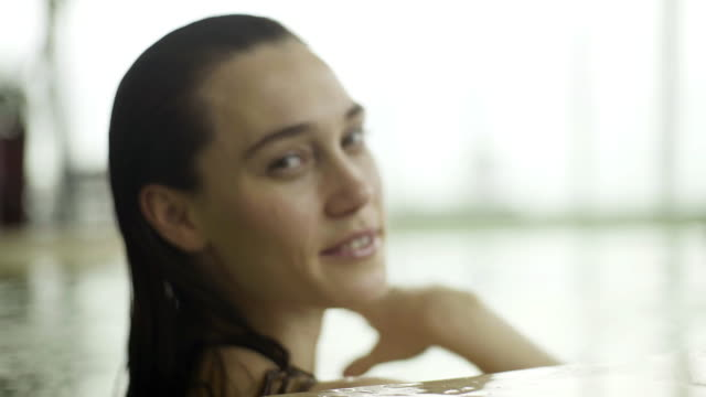 stockvideo's en b-roll-footage met young woman swimming to pool edge and smiling at camera - binnenbad