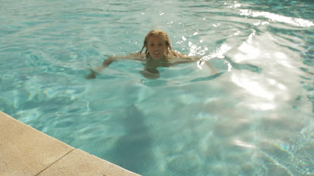 stockvideo's en b-roll-footage met young woman swimming to side of pool - buitenbad