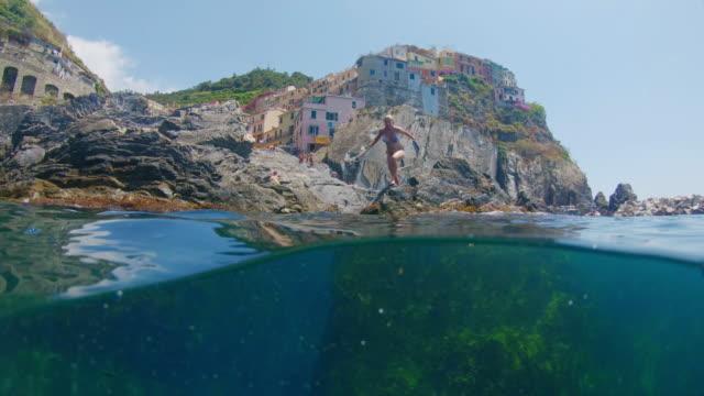 ms young woman swimming underwater in sea, cinque terre, italy - scogliera video stock e b–roll