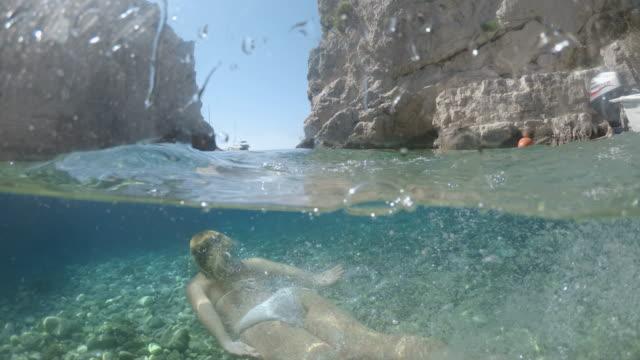 日当たりの良いアドリア海、クロアチアで水中を泳ぐmsの若い女性 - 水中カメラ点の映像素材/bロール