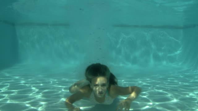 young woman swimming underwater - ビキニ点の映像素材/bロール