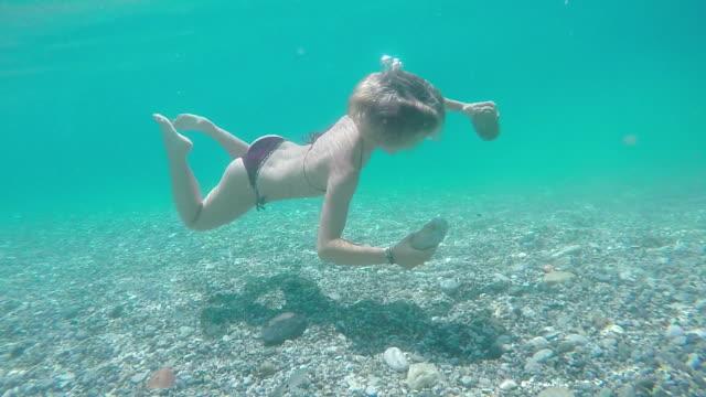vídeos de stock, filmes e b-roll de jovem mulher nada através de mar tranquilo, pega em rochas, em seguida, continua - prendendo a respiração