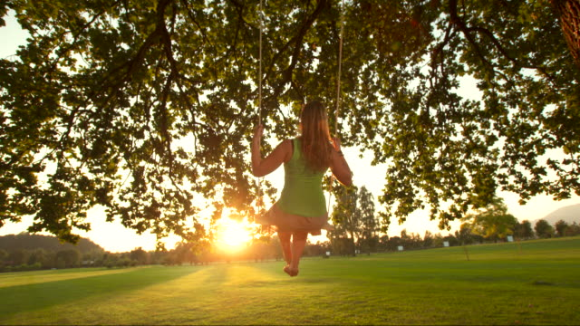 HD SLOW MOTION: Young Woman Swinging At Sunset