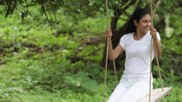 Young woman swinging in a park, Malshej Ghat, Maharashtra, India
