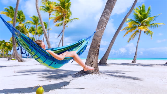 ms young woman swinging in hammock at tropical beach - palm tree stock videos & royalty-free footage
