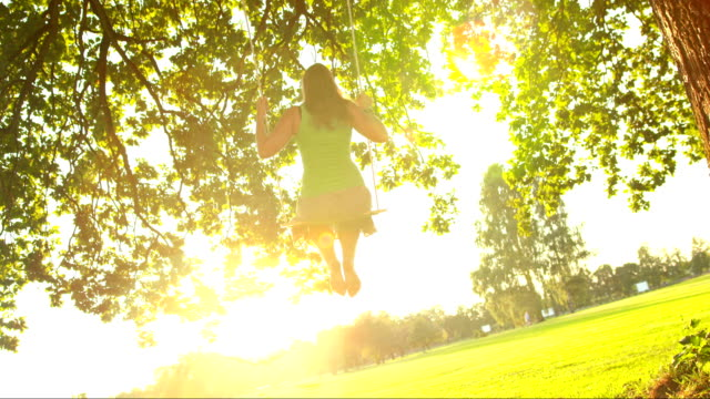 HD SLOW MOTION: Young Woman Swinging In Sunlight