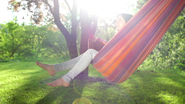 Young woman swinging on a hammock under the trees
