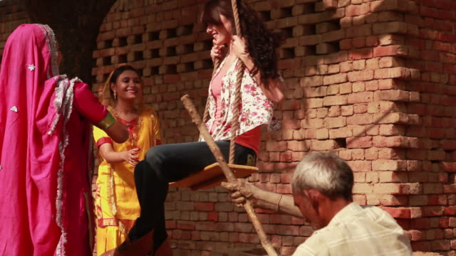 young woman swinging on a rope swing in a village, haryana, india - 揺れる点の映像素材/bロール