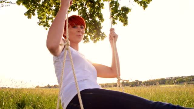 SLO MO Young woman swinging on a tree swing