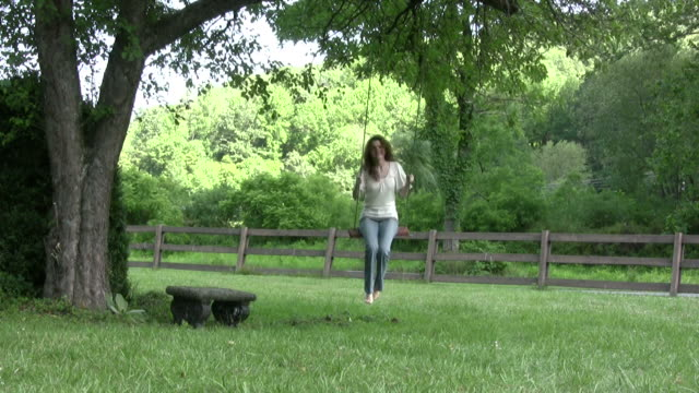 young woman swings on a rope swing - rope swing stock videos & royalty-free footage