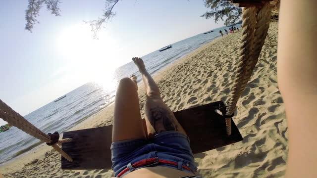 vidéos et rushes de jeune femme oscille sur une chaise en bois au-dessus de la plage, mer - balançoire