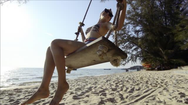 Jeune femme oscille sur une chaise en bois au-dessus de la plage, mer
