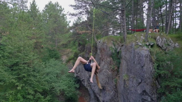 a young woman swings while slacklining on a tightrope in the mountains. - tightrope stock videos & royalty-free footage