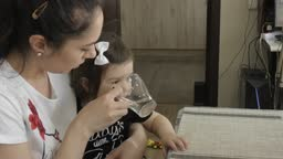 A young woman takes a glass and gives the child a drink..