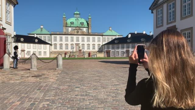a young woman takes a photo of frederiksborg castle, hillerød, denmark - öresundregion stock-videos und b-roll-filmmaterial
