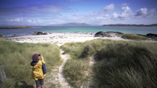 stockvideo's en b-roll-footage met a young woman takes a picture of the crystal clear blue waters of iona, scotland. on a clear summer afternoon. - eiland