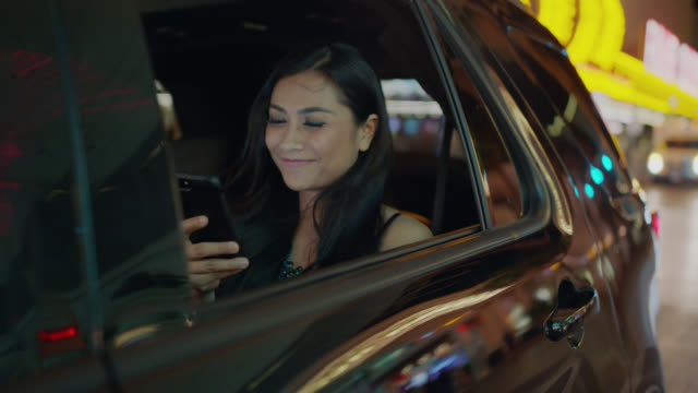 vidéos et rushes de young woman takes a picture of the neon lights of the las vegas strip out of her window in the backseat of a black suv then smiles at her phone - passager
