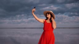 young woman takes a selfie in a beautiful unusual place. girl in a red dress, hat and sunglasses on a pink lake.