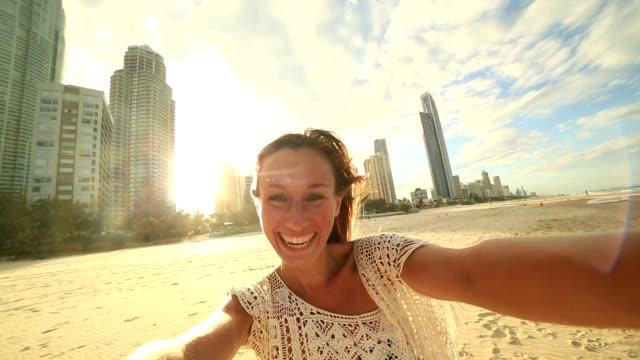 vídeos y material grabado en eventos de stock de joven toma un retrato selfie en la playa de paraíso de los surfistas - gold coast