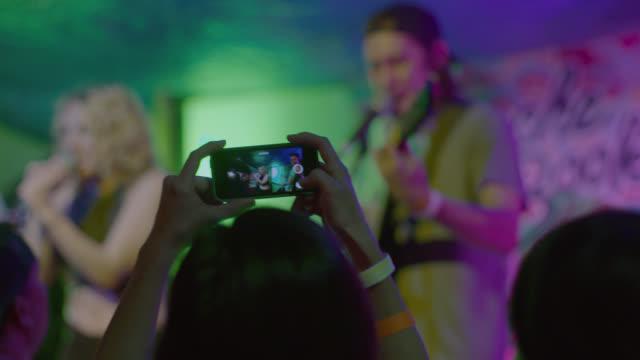 vídeos y material grabado en eventos de stock de young woman takes a video with smartphone of band performing at outdoor rock concert - guitarrista