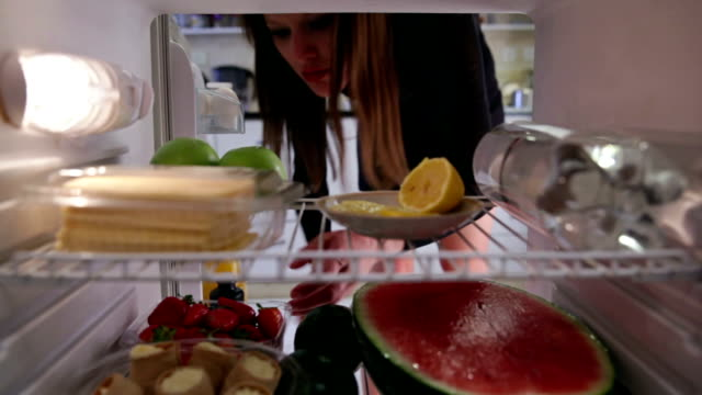 young woman  takes cake from the fridge - refrigerator stock videos & royalty-free footage