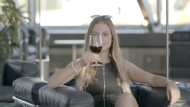young woman takes drink of wine in airport - cross legged stock videos & royalty-free footage