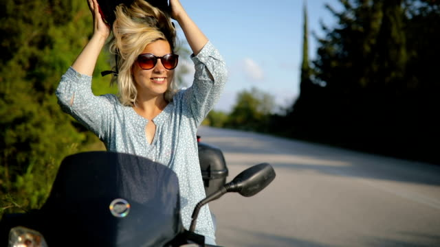 Young woman takes off her crash helmet