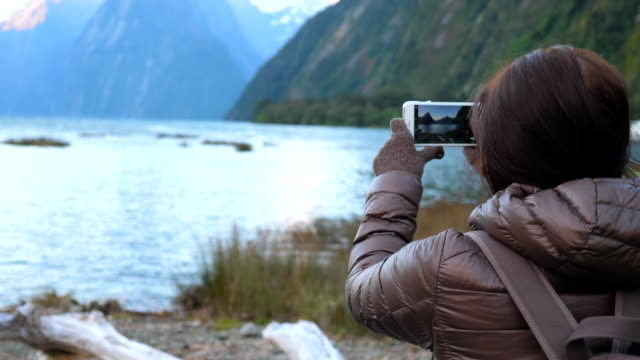 young woman takes photo at milford sound, new zealand - famous place stock videos & royalty-free footage
