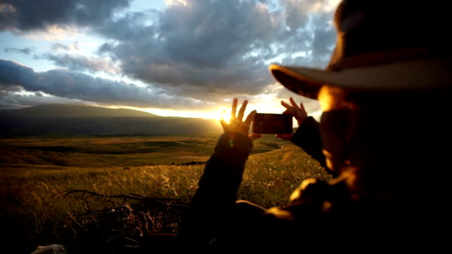 Young woman takes photo of steppe sunset