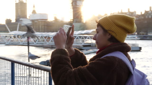 vídeos y material grabado en eventos de stock de young woman takes photos with tablet at thames embankment, slow motion. - rodear