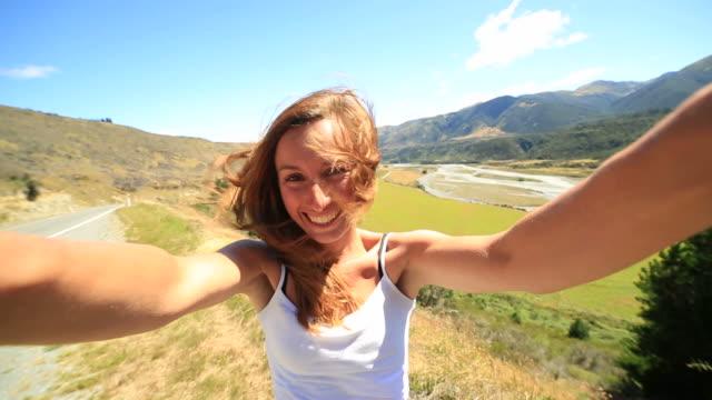 vídeos de stock e filmes b-roll de jovem mulher toma auto-retrato em um dia de vento-nova zelândia - cultura jovem