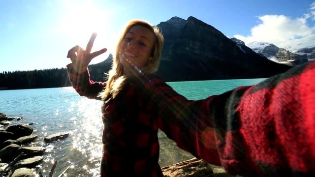 vídeos y material grabado en eventos de stock de mujer joven toma selfie en lake louise - vanidad