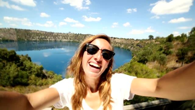 Young woman takes selfie portrait at Blue lake, South Australia