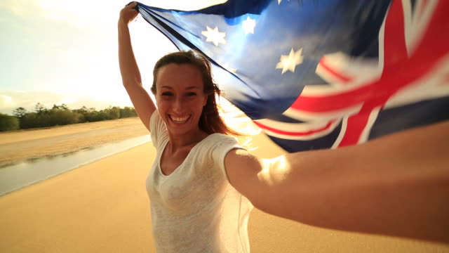 Young woman takes selfie portrait on beach with Australian flag
