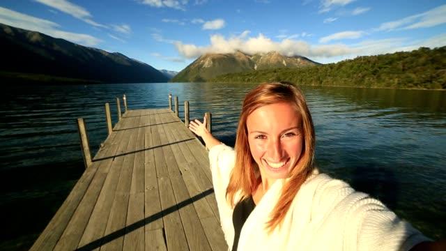 Young woman takes selfie portrait on lake pier