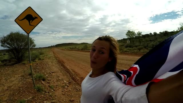 young woman takes selfie portrait on road next to kangaroo warning sign - road warning sign stock videos & royalty-free footage
