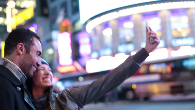 young woman takes smartphone photo kissing boyfriend on cheek in times square - boyfriend stock videos & royalty-free footage