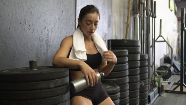 ms young woman taking a break while working out in a gym - riposarsi video stock e b–roll