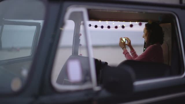 young woman taking a photo from her camper van - photography stock videos & royalty-free footage