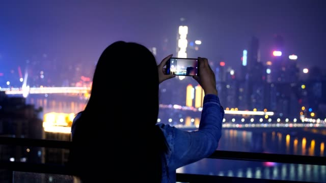young woman taking a photo of city night view - photography stock videos & royalty-free footage