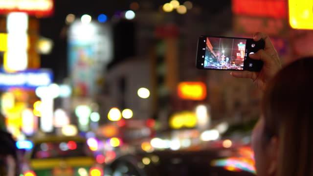 vidéos et rushes de jeune femme prend une photo de paysage urbain - photophone