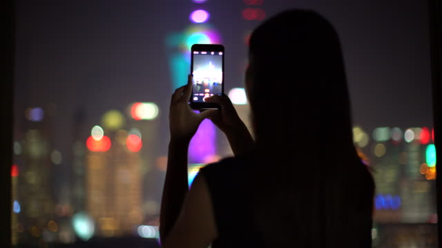 MS young woman taking a photo of Shanghai skyline at night