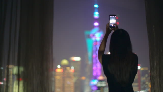 MS young woman taking a photo of Shanghai skyline, China