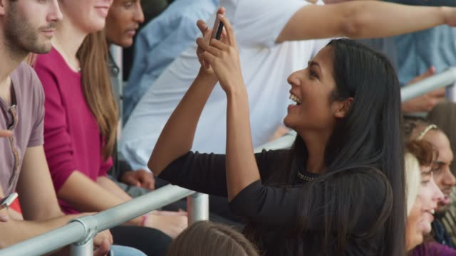 young woman taking a photo of the people on the stadium tribune and smiling - avvenimento sportivo video stock e b–roll
