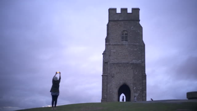 A young Woman taking a picture of Glastonbury Tor on a cloudy windy afternoon.